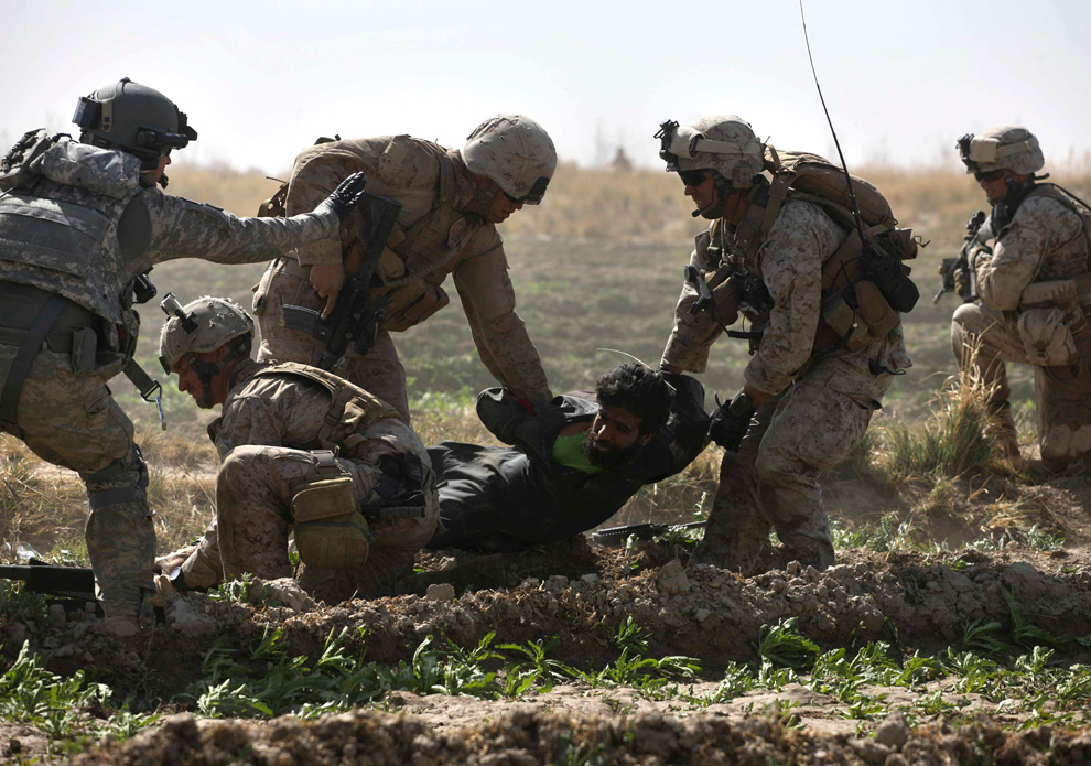 6. Во время единичной перестрелки с талибами штабной сержант и медик Роберт Б. Коудри (крайний слева) руководит операцией по эвакуации оказывающего сопротивление раненого боевика, который был схвачен за несколько минут до того, как был сделан снимок, в Маржахе 17 февраля. (AP Photo/Brennan Linsley)