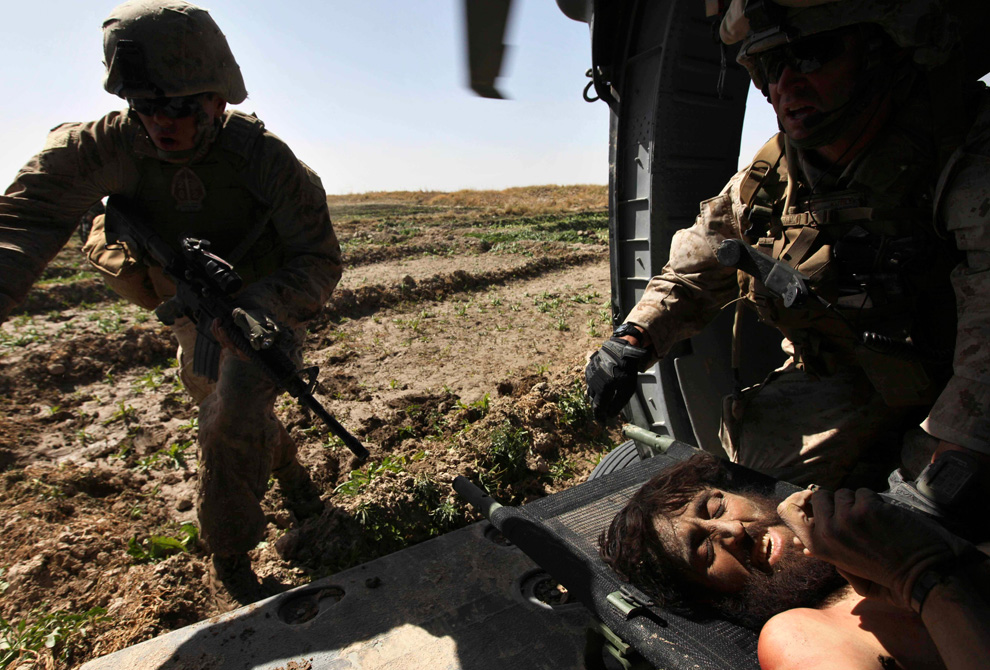 7. Морпехи охраняют одного из двух раненых боевиков «Талибана» в Маржахе 17 февраля. Боевиков доставили в близлежащий полевой госпиталь. Военно-медицинский вертолет «Пегас» эвакуировал раненых с поле боя во время перестрелок солдат с талибами, в результате чего сам не раз попадал под обстрел. (AP Photo/Brennan Linsley)