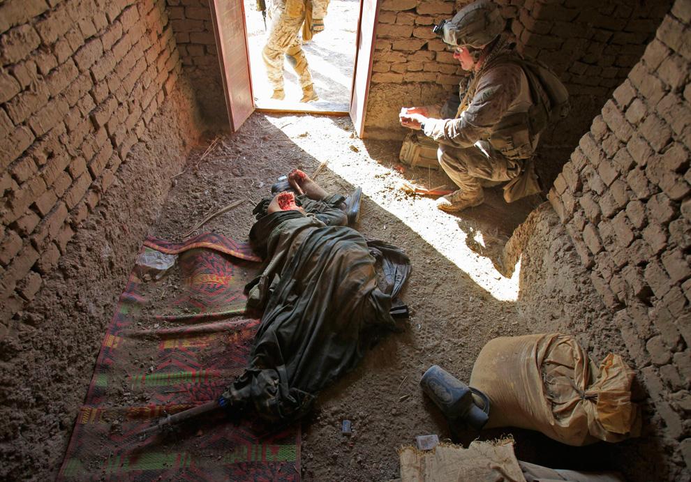 8. Морпех из подразделения «Браво» первого батальона присел у тела убитого талиба в Маржахе в районе Над Али 18 февраля. (REUTERS/Goran Tomasevic)