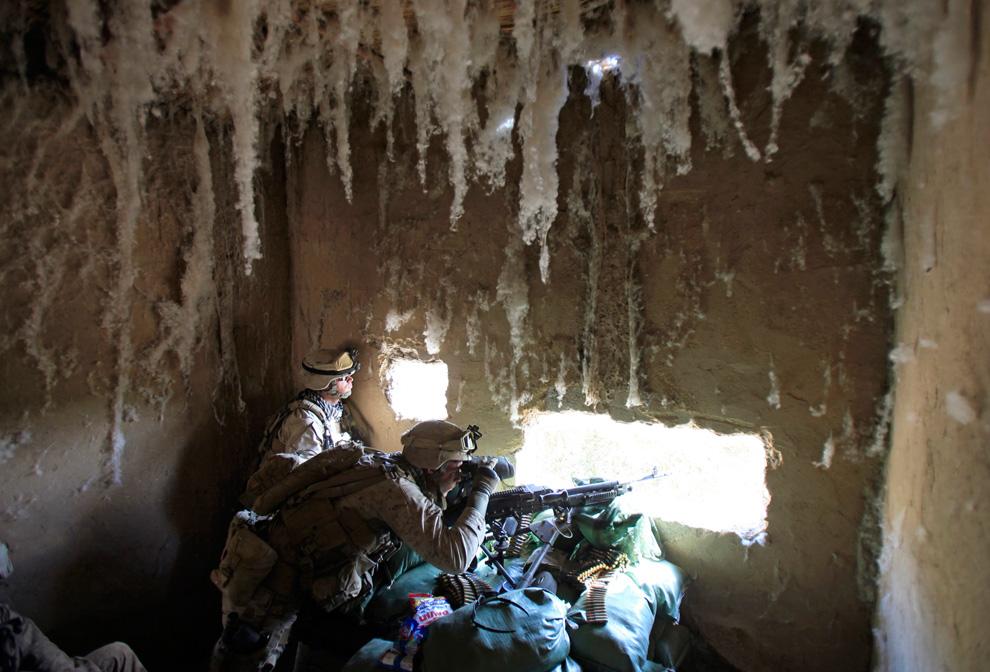 10. Солдаты подразделения «Браво» первого батальона высматривают снайпера из «Талибана» из мастерской по обработке хлопка в Маржахе 19 февраля. (REUTERS/Goran Tomasevic)
