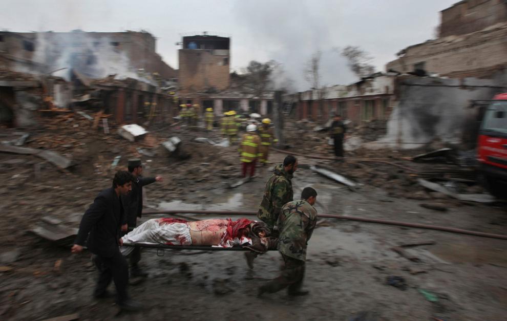 13. Афганский солдаты и полицейские уносят окровавленное тело неизвестного с места взрыва и перестрелки в Кабуле 26 февраля. (AP Photo/Altaf Qadri)