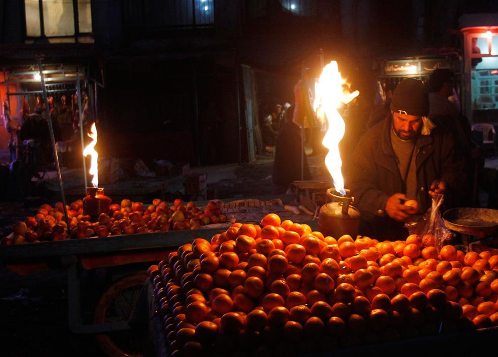 14. Мужчина выбирает апельсины поздним вечером на рынке в Кабуле 20 февраля. (AP Photo/Rahmat Gul)