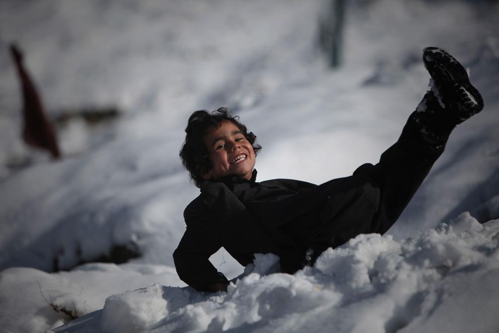 16. Афганский мальчик по имени Сахил смеется, поскользнувшись на снегу в Кабуле 8 февраля. (AP Photo/Altaf Qadri)