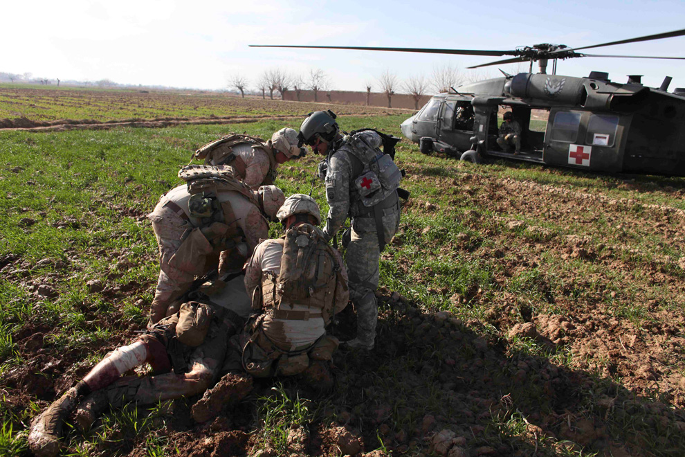 21. Полевой медик штабной сержант Роберт Б. Коудри (справа) из подразделения «Чарли» эвакуирует морпеха, раненого в результате обстрела из гранатомета, в Маржахе 13 февраля. (AP Photo/Brennan Linsley)