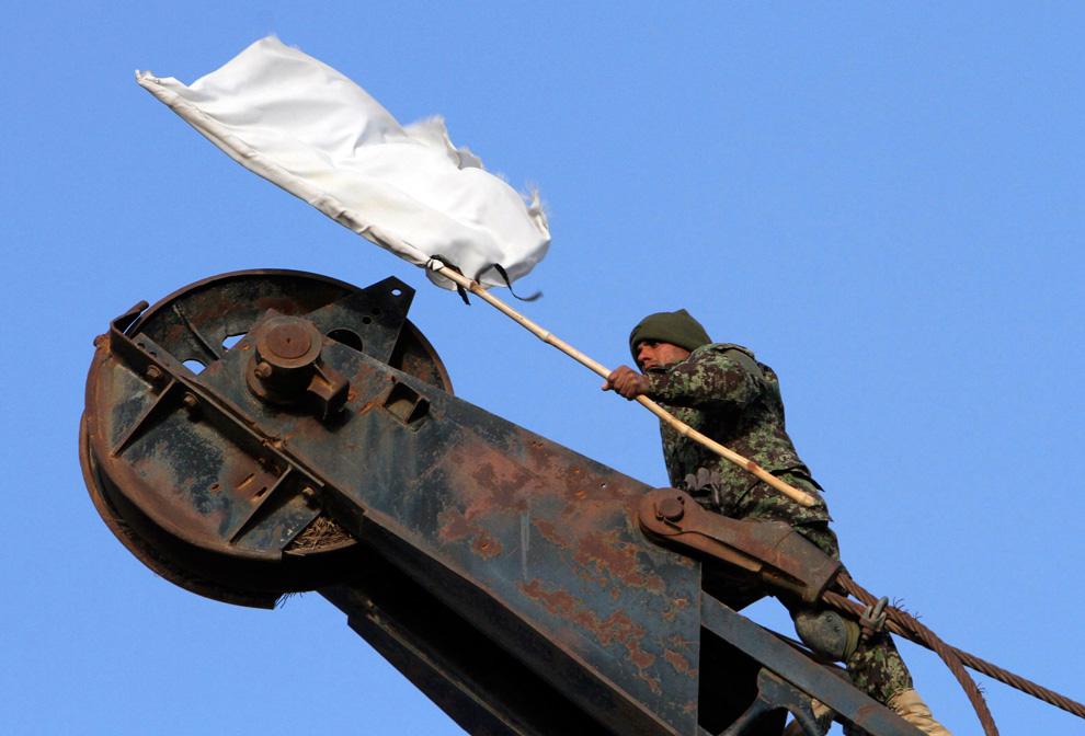 22. 22-летний рядовой Азиз Ватандосд из второго подразделения первого батальона Афганской национальной армии залез на кран, чтобы убрать белый флаг талибов и поднять афганский флаг в бывшем опорном пункте сопротивления «Талибана» 15 февраля в Шовале. Район охраняли британские и афганские войска. (REUTERS/Julian Simmonds)