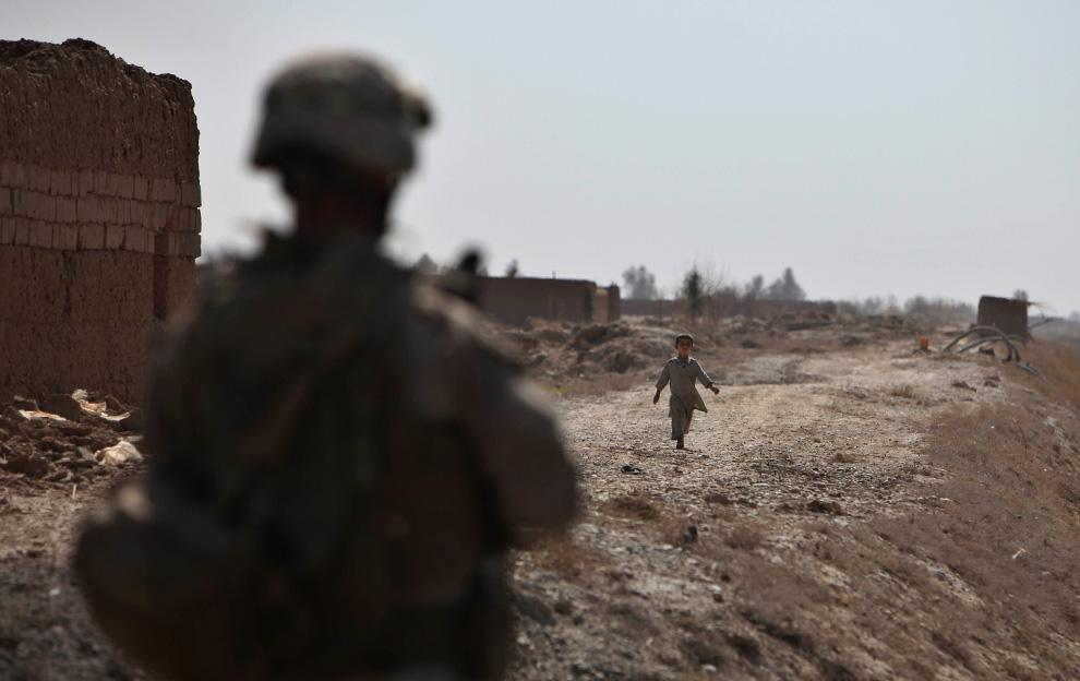 27. Мальчик идет мимо солдата НАТО в Маржахе 17 февраля. (AP Photo/Altaf Qadri)