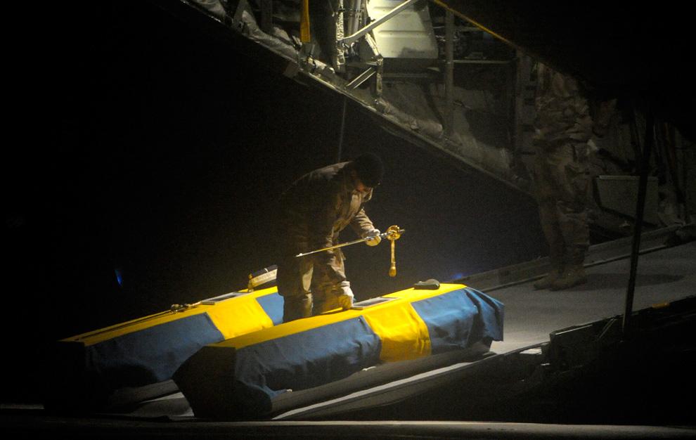 29. Гробы двух шведских солдат – капитана Йохана Палмлова и лейтенанта Гуннара Андерссона – выгрузили из самолета шведских ВВС «C-130 Hercules» по прибытии в аэропорт «Арна» в Упсале 10 февраля. Два шведских солдата и афганский переводчик погибли 7 февраля, когда на их отряд напали в северной части Афганистана. Эта атака увеличила число погибших шведских солдат до четырех с тех пор, как Швеция начала отсылать солдат в Афганистан в 2001 году. (ANDERS WIKLUND/SCANPIX/AFP/Getty Images)