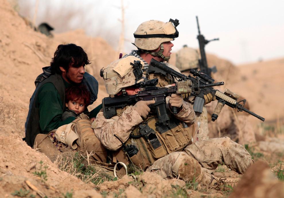 30. Морпех из подразделения «Браво» первого батальона защищает афганца с ребенком после того, как талибы открыли огонь в городе Маржах 13 февраля. (REUTERS/Goran Tomasevic)