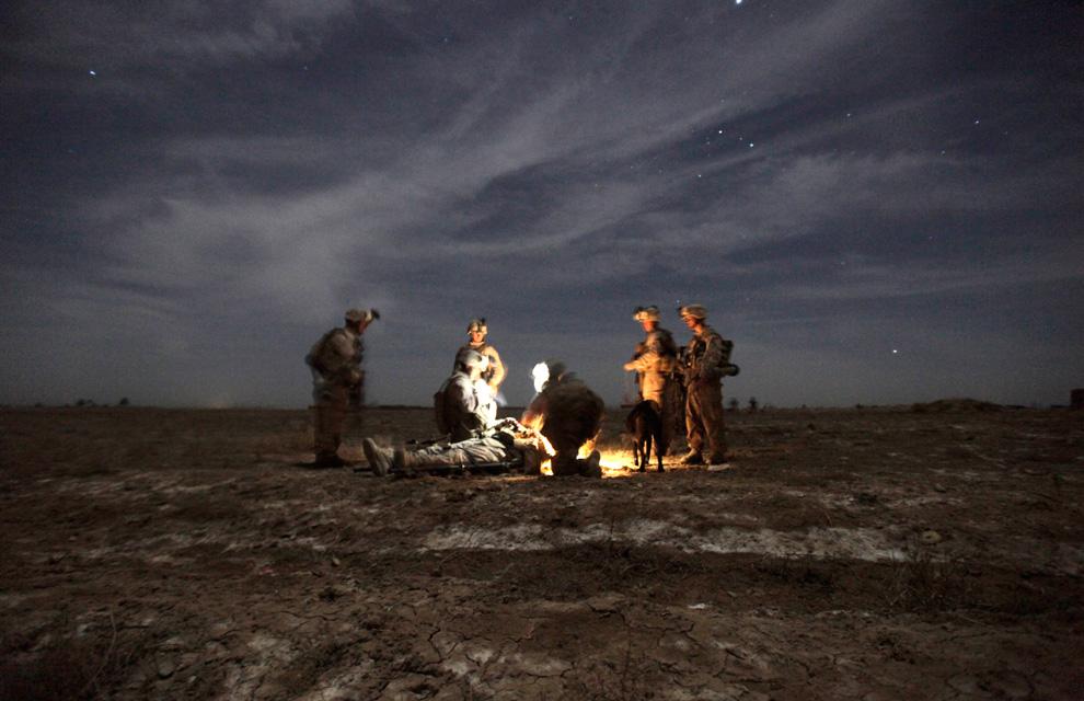 36. Морпехи из подразделения «Чарли» оказывают товарищу первую медицинскую помощь в ожидании санитарного вертолета. Их бронетранспортер с усиленной противоминной защитой наехал на самодельное взрывное устройство в Трикх Навар на северо-востоке Маржаха 23 февраля. Три взорвавшиеся бомбы ранили трех морпехов во время зачистки подразделением «Чарли» участка дороги в 4 км от Лашкар Гаха до Маржаха. (PATRICK BAZ/AFP/Getty Images)