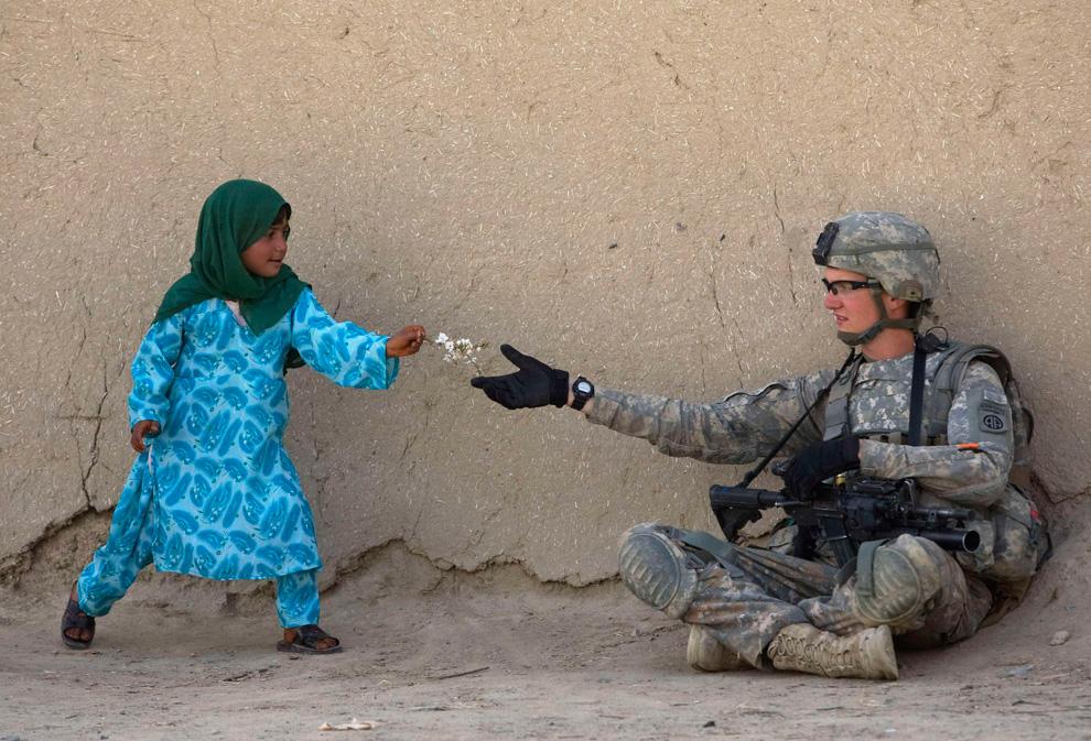 39. Афганская девочка дарит цветок рядовому первого класса Дэнни Комли во время патрулирования долины Аргандаб в провинции Кандагар 24 февраля. (REUTERS/Baz Ratner)