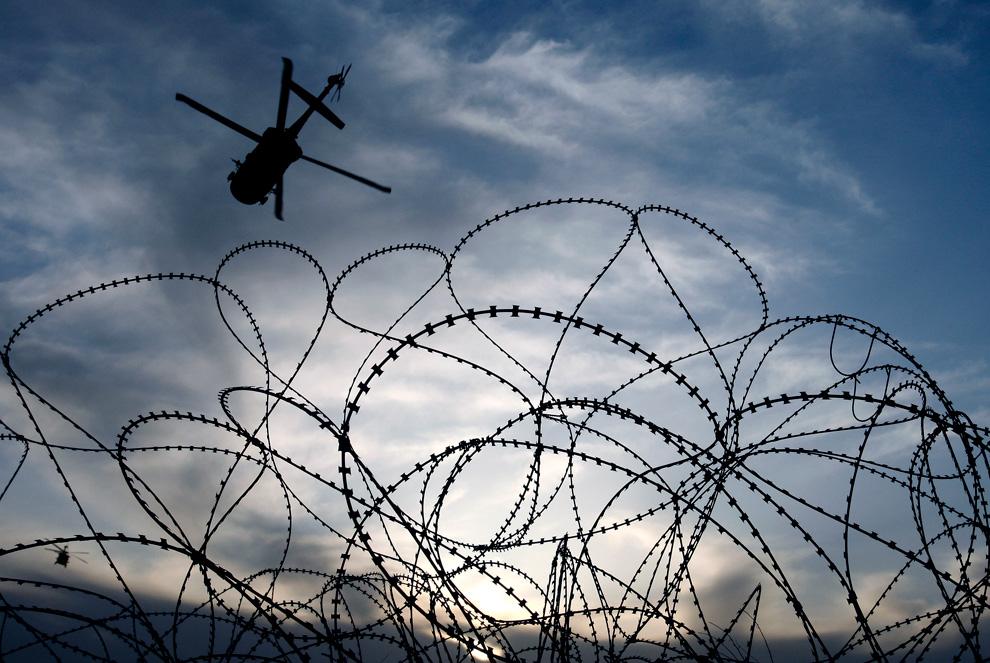 40. Военный вертолет, заходящий на посадку на аэродроме Кандагар, виден через колючую проволоку 31 января. (AP Photo/Kirsty Wigglesworth)
