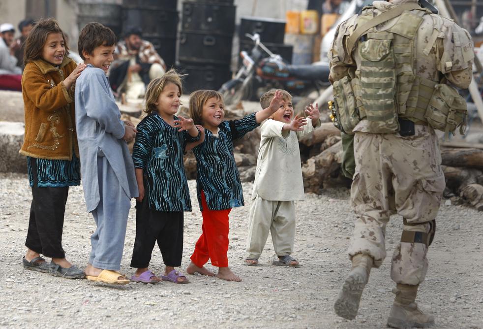 1. Афганские дети машут капралу Джессе Старко из Эдмонтона, штат Альберта, из Канадской резервистской армии при Канадских легкий пехотных войсках принцессы Патрисии, который проходит мимо во время операции в Кандагаре 21 января. (AP / Kirsty Wigglesworth)