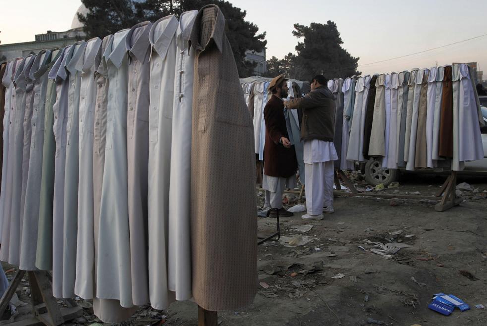 10. Торговец подержанной одеждой проверяет размер клиента на рынке в Кабуле 25 января. (AP / Musadeq Sadeq)