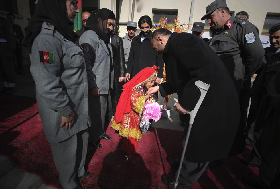 13. Афганская девочка в традиционном наряде целует руку афганского министра внутренних дел Мохаммеда Ханифа Атмара, который прибыл, чтобы отдать должное полицейским, вовремя среагировавшим на атаку боевиков «Талибана» в центре Кабула, 25 января. (AP / Altaf Qadri)