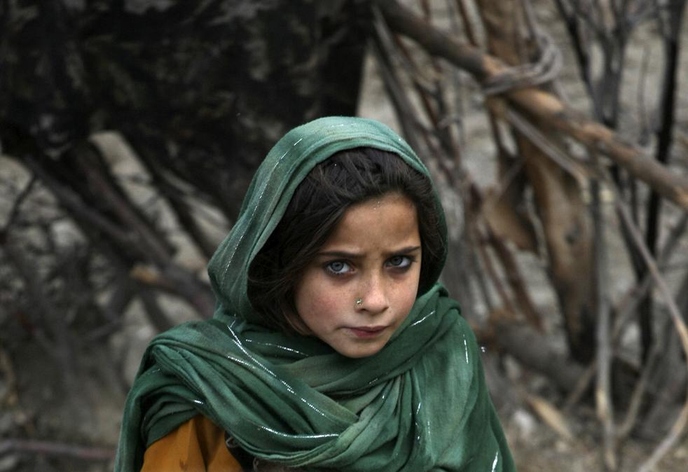 14. Афганская девочка в деревне Галбалай в долине Пех, провинция Кунар, северо-восток Афганистана, 23 января. Девочка смотрит, как офицеры армии США разговаривают с ее отцом – местным старейшиной – во время патрулирования. ( AP / Brennan Linsley)