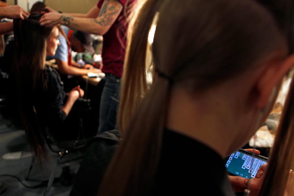 16. Модель раскладывает пасьянс на телефоне, пока стилисты и визажисты готовят ее к выходу на подиум для показа коллекции от «Halston» в Нью-Йорке. (AP Photo/David Goldman)