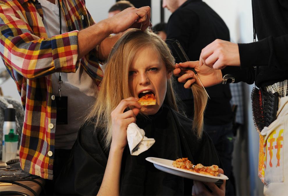 29. Модель кушает пиццу, пока ей укладывают волосы перед началом показа коллекции от Донны Каран 15 февраля в Нью-Йорке. (STAN HONDA/AFP/Getty Images)