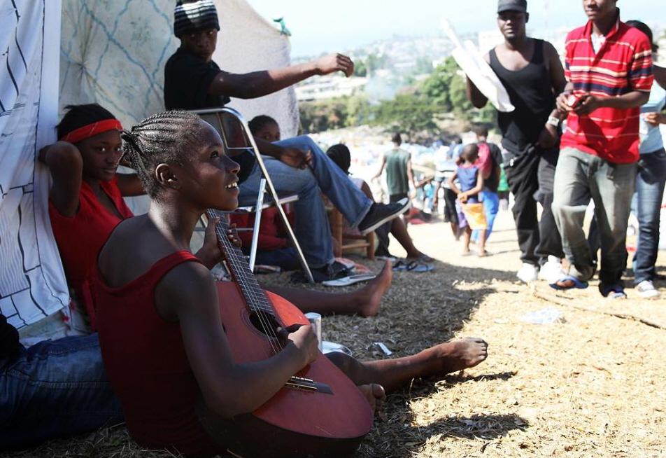 3. Девушка играет на гитаре в лагере для беженцев Дельмас 40В, где живет более 25 000 человек, оставшихся без крова, 22 января. (Julien Tack, AFP / Getty Images)