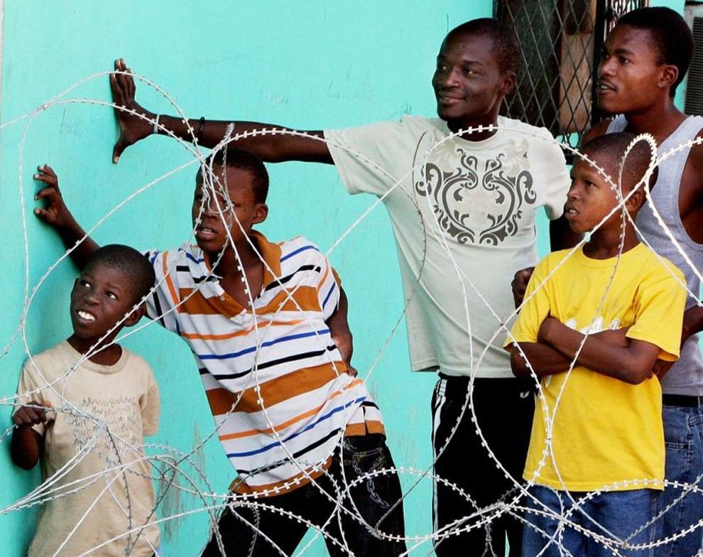 10. Колючая проволока отделяет мальчиков от территории медицинской клиники, где расположился лагерь для беженцев . (Chuck Liddy, Raleigh News & Observer / MCT)