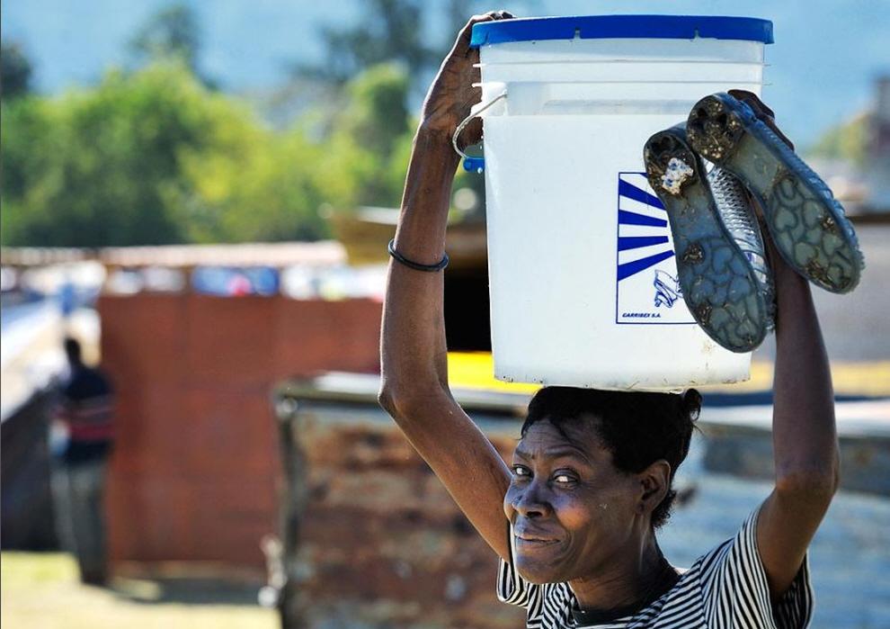 11. Женщина улыбается, неся питьевую воду во временный лагерь в районе Белэйр в Порт-о-Пренс. В районе впервые поступила вода , когда Норвежская церковная организация установила здесь водопровод для бездомных семей. (Paul Jeffery, ACT Alliance / MCT)
