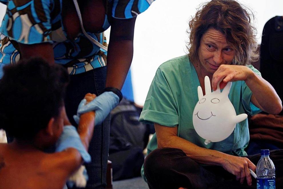12. Медсестра из Майями 46-летняя Лиана Голд (справа) пытается развеселить 6-летнюю Мардошу Феври (слева) в лагере ООН недалеко от аэропорта  в Жакмеле. (Carl Juste, The Miami Herald / AP)