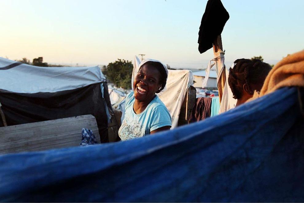 13. Женщина смеется возле своей палатки  в Порт-о-Пренс. (Joe Raedle, Getty Images)