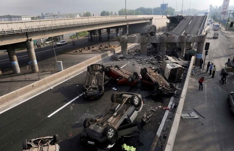 1. Перевернутые автомобили валяются на шоссе в Сантьяго 27 февраля 2010. (REUTERS/Marco Fredes)