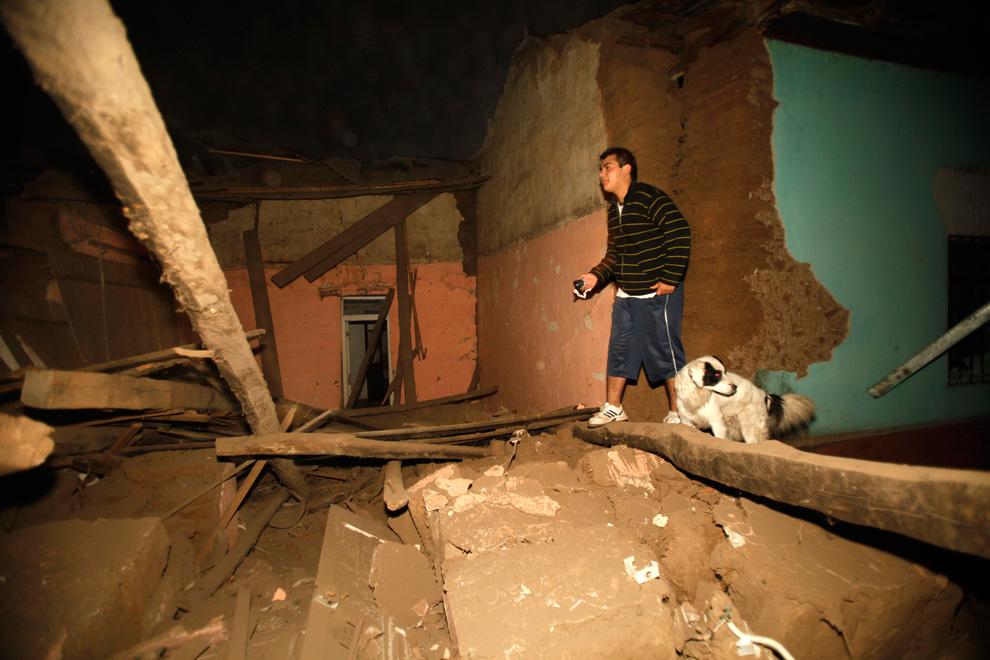 2. Житель чилийского города Талька идет среди обломков разрушенного дома. (AP Photo/Roberto Candia)