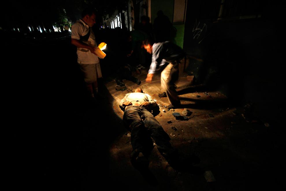 3. Местные жители стоят над трупом, лежащим на улице в городе Талька, расположенном примерно в 275 километрах к югу от Сантьяго. (AP Photo/Roberto Candia)