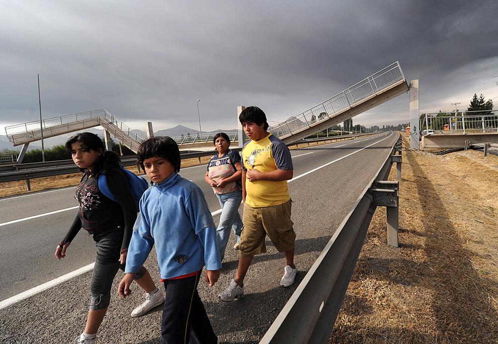 5. Люди идут вдоль шоссе на фоне рухнувшего моста в окрестностях Сантьяго. (MARTIN BERNETTI/AFP/Getty Images)