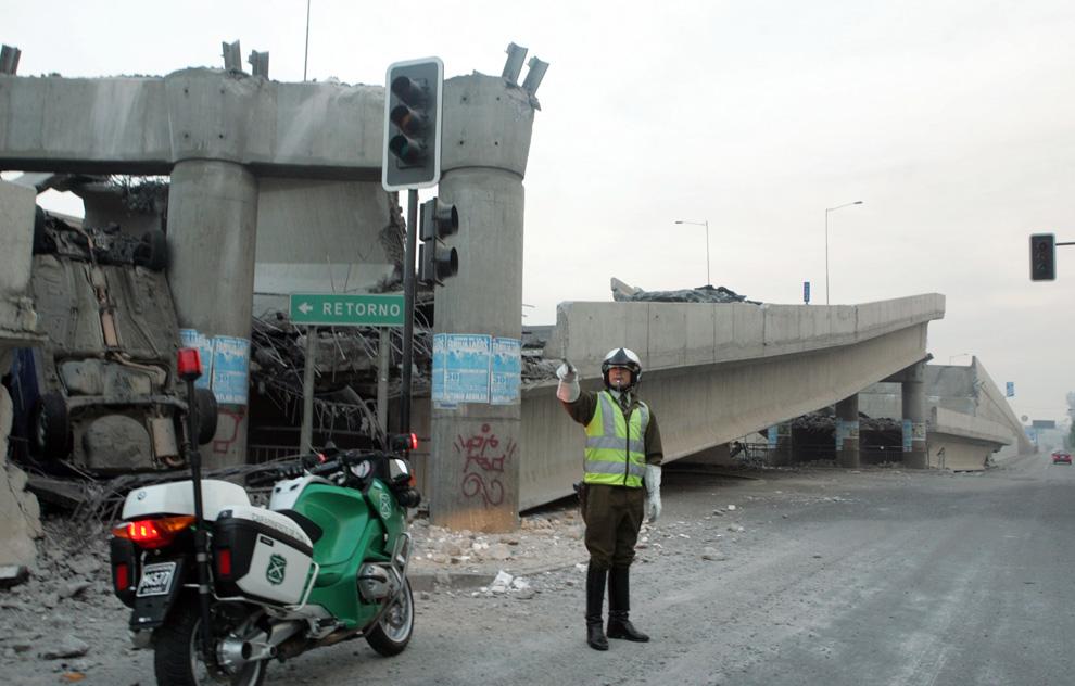6. Полицейский управляет дорожным движением рядом с рухнувшей автомагистралью на эстакаде в Сантьяго. (AP Photo/David Lillo)