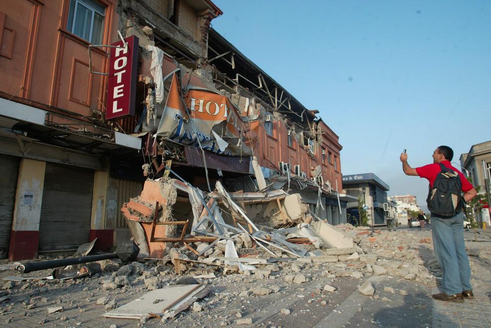 8. Местный житель фотографирует разрушенное здание в чилийском городе Талька. (AP Photo/Sebastian Martinez)