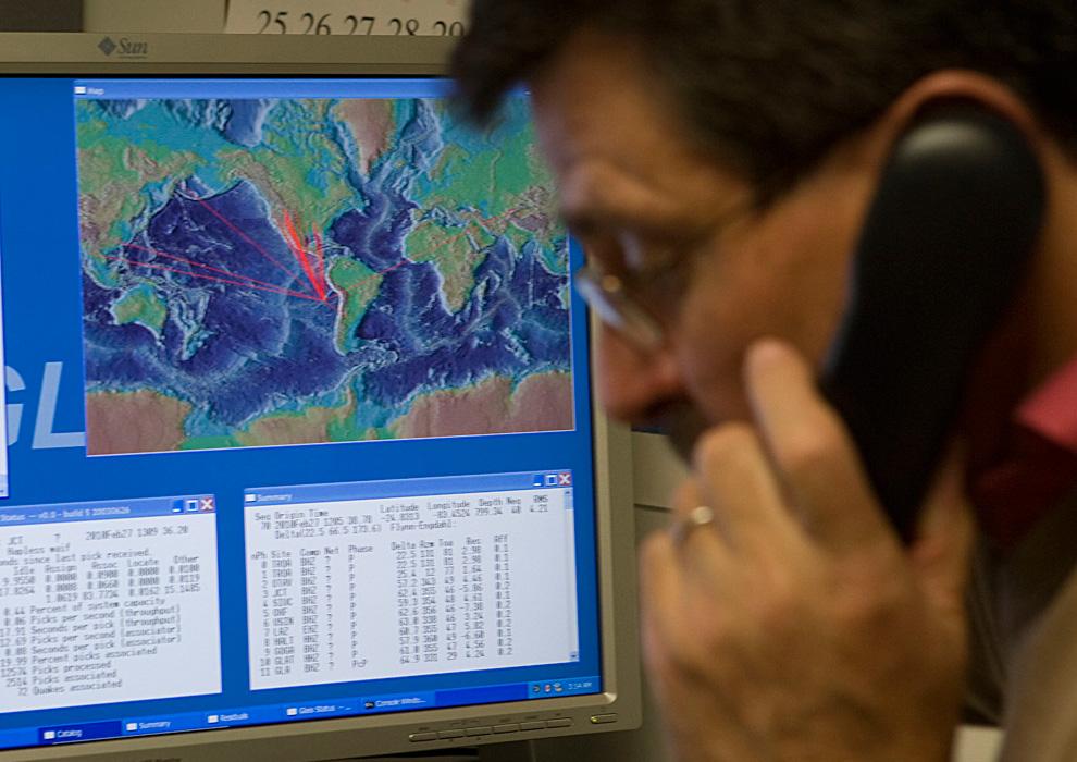 9. На графике показаны возможные пути волн цунами, которые были вызваны землетрясением в Чили. Рядом с компьютером д-р Чарльз МакКрири говорит по телефону в Центре предупреждения о цунами Тихоокеанского региона. (AP Photo/Marco Garcia)