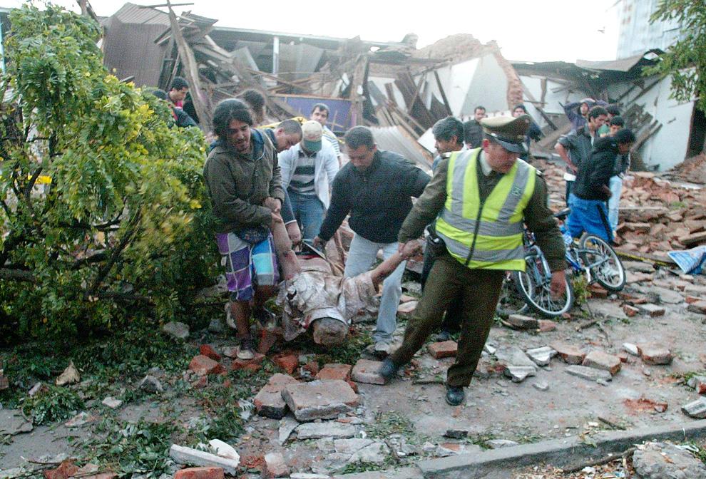 10. Офицер полиции и местные жители выносят труп из разрушенного дома в чилийском городе Талька. (AP Photo/Sebastian Martinez)