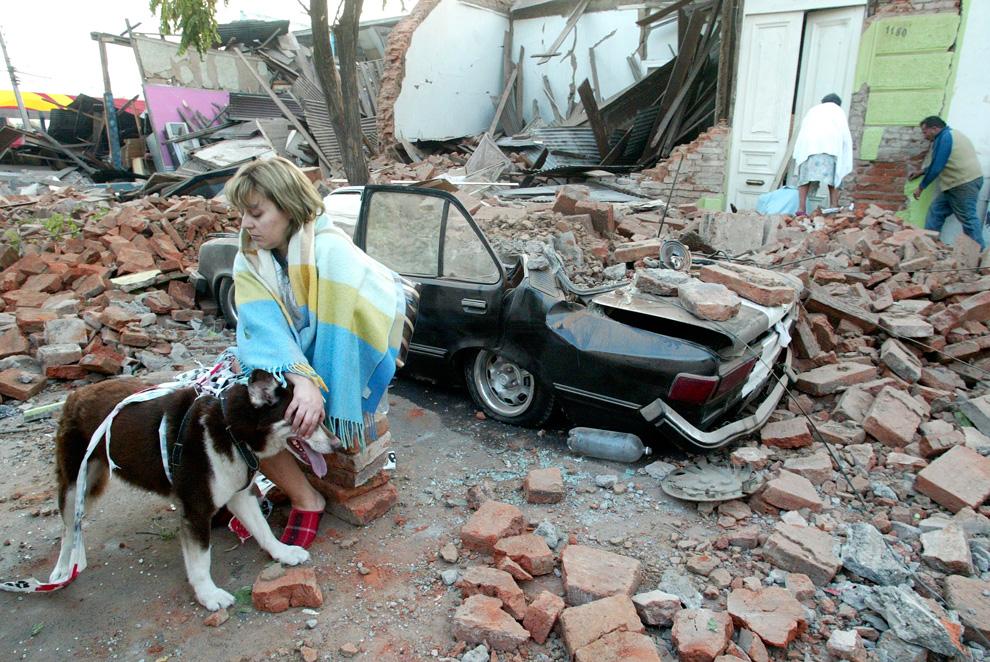 12. Женщина сидит перед домами поврежденными землетрясением в городе Талька. (AP Photo/Sebastian Martinez)