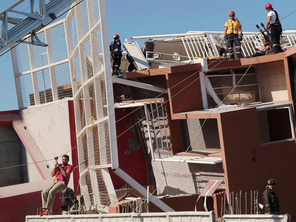 14. Спасатели спускают на тросах одного из выживших, которого нашли в рухнувшем жилом комплексе после землетрясения в городе Консепсьон. (REUTERS/Jose Luis Saavedra)