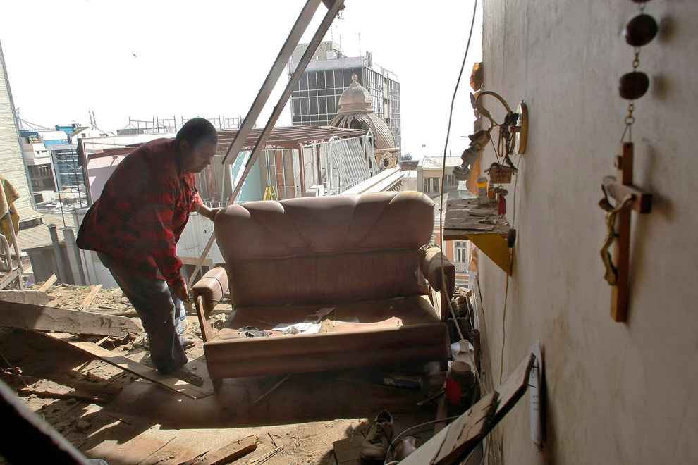 15. Мужчина выносит вещи из своего разрушенного дома в Вальпараисо. (REUTERS/Eliseo Fernandez)