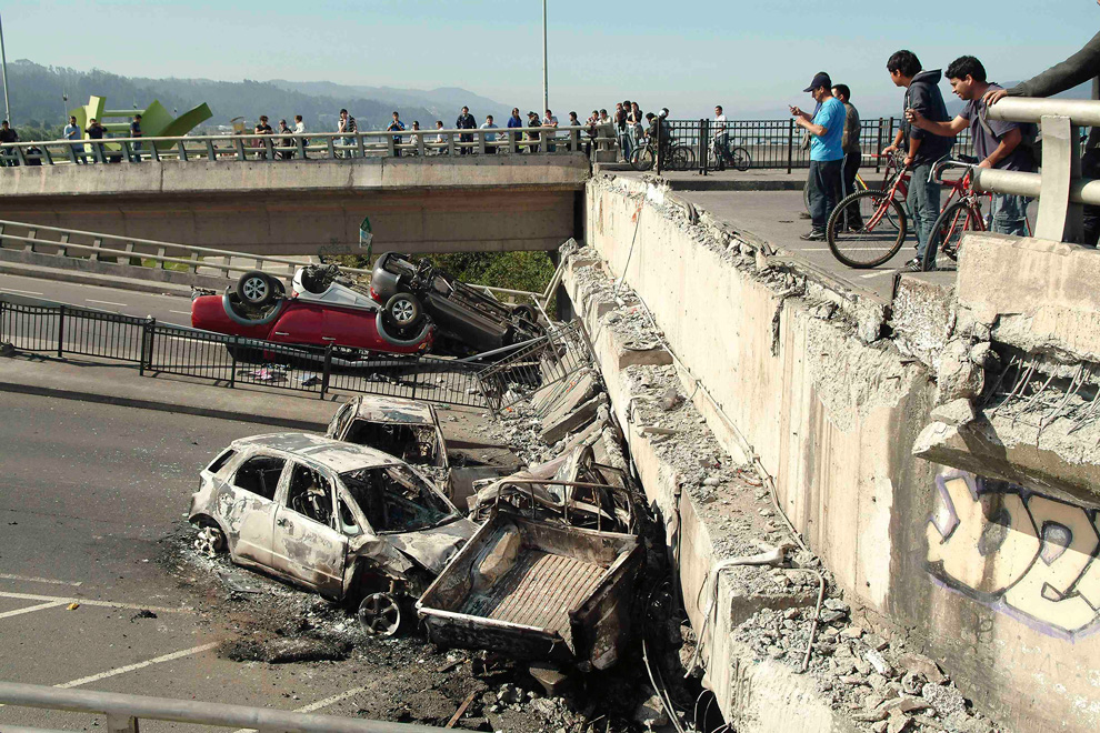 17. Люди смотрят на шоссе разрушенное землетрясением и покороеженные автомобили в городе Консепсьон. (REUTERS/Jose Luis Saavedra)