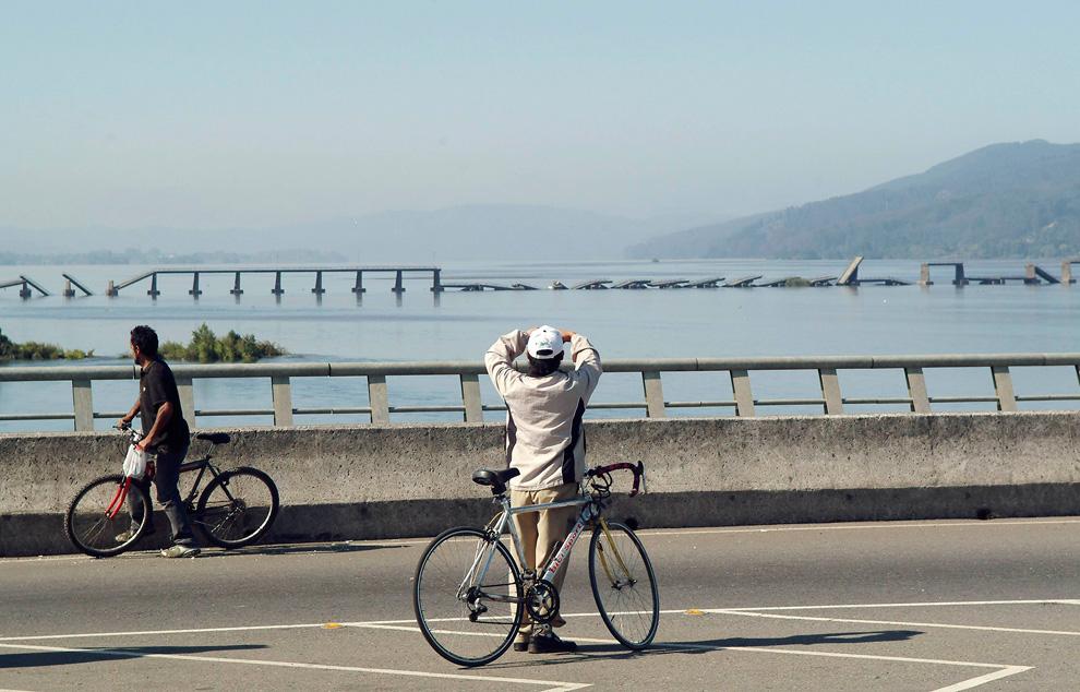 18. Велосипедист смотрит на мост, который рухнул в результате землетрясения в городе Консепсьон. (REUTERS/Jose Luis Saavedra)