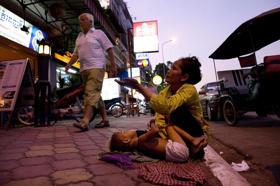 22. Мать Ворн и ее сын Коав просят милостыню у туристов в Пномпене, Камбоджи, 5 февраля. (Getty Images / Paula Bronstein)