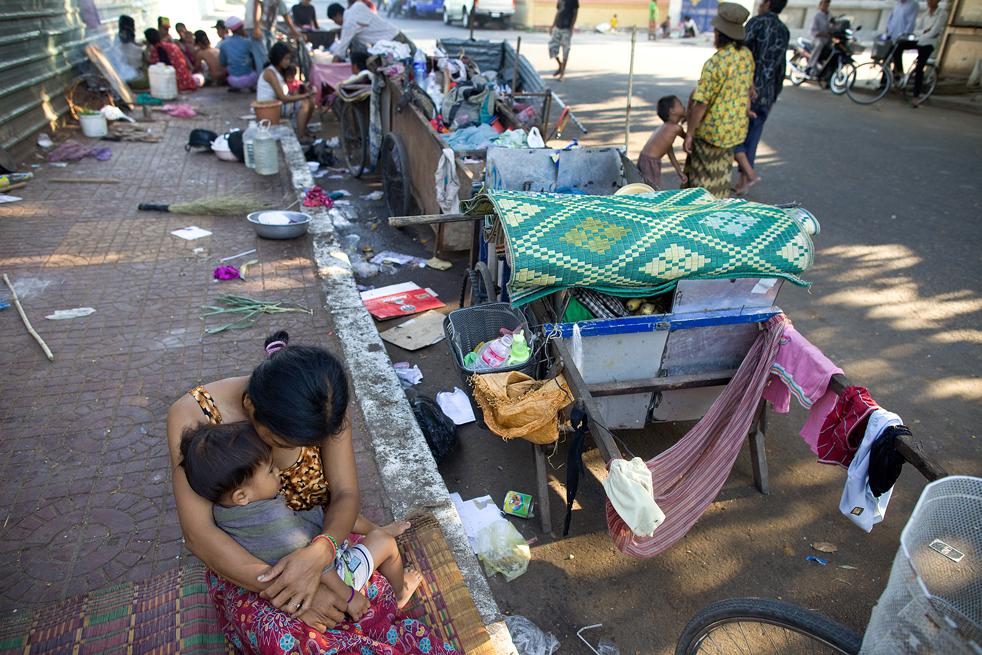 2. Мать сидит на улице со своим сыном 6 февраля в Пномпене. Они спят на улице с 30 другими семьями, которые выживают благодаря тому, что просят милостыню, собирают мусор и продают еду. (Getty Images / Paula Bronstein)