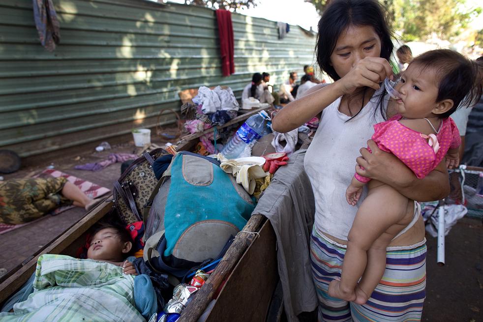 3. Мать кормит ребенка, пока второй спит в мусорном баке на улице в Пномпене. (Getty Images / Paula Bronstein)