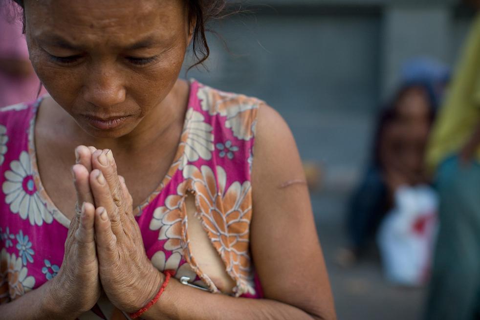 4. Камбоджийка молится иностранцу, прося денег, 7 февраля. (Getty Images / Paula Bronstein)