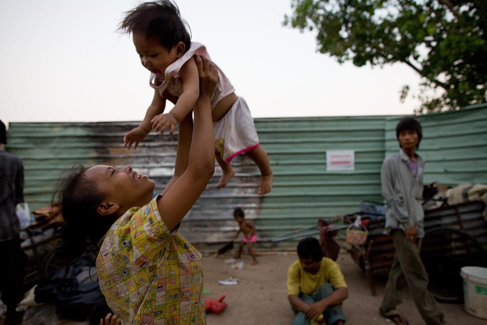 5. Мать играет со своим ребенком на улице в Пномпене. (Getty Images / Paula Bronstein)