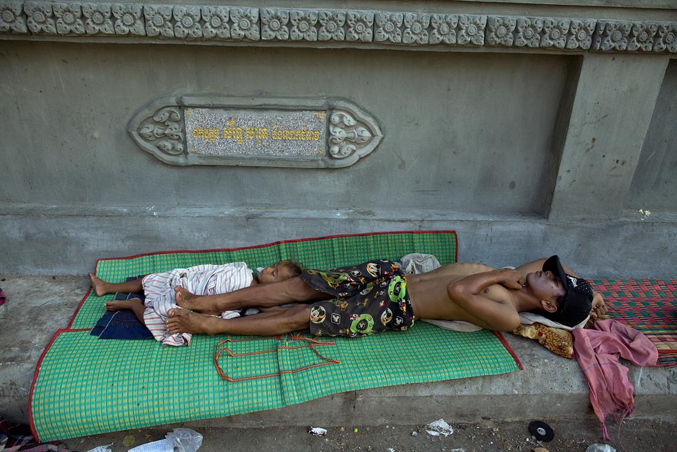 10. Бездомный человек по имени Бросс спит на тротуаре рядом со своим сыном 6 февраля в столице Камбоджи. (Getty Images / Paula Bronstein)