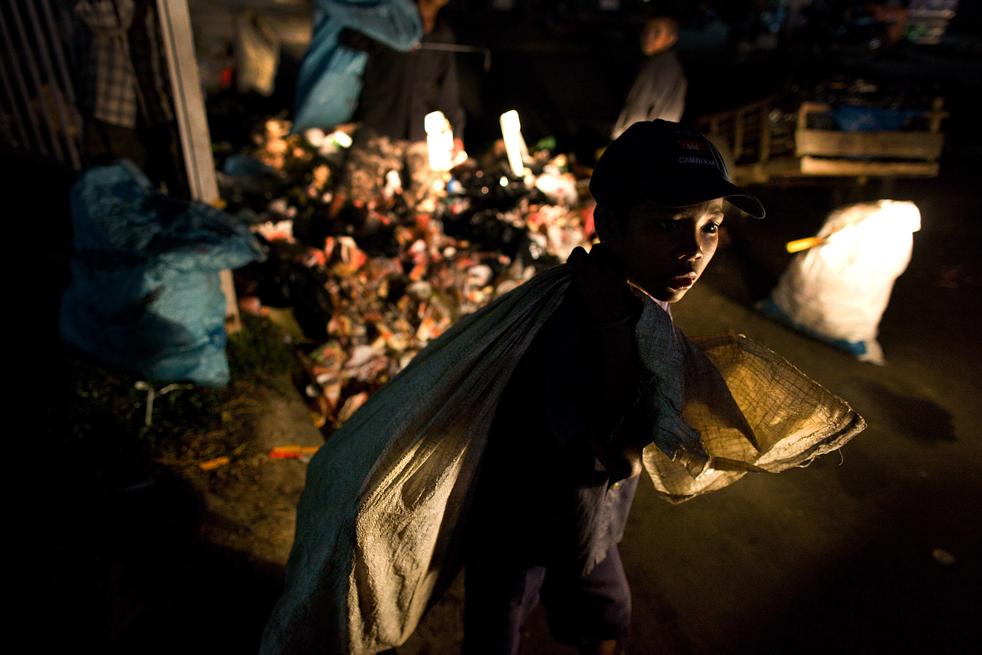 13. Камбоджийский мальчик собирает мусор после закрытия магазинов на улице в Пномпене 4 февраля. (Getty Images / Paula Bronstein)