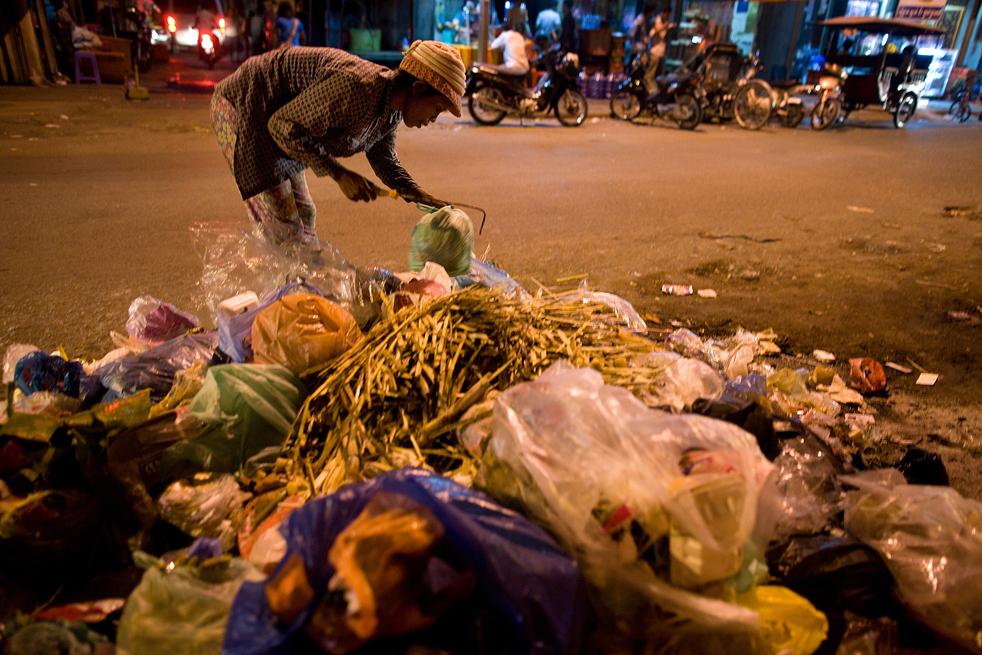 14. Камбоджийская женщина собирает мусор после закрытия магазинов. Этим она и зарабатывает себе на жизнь. (Getty Images / Paula Bronstein)