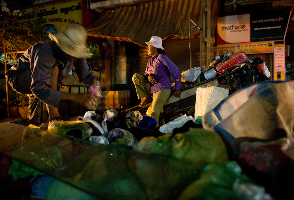 15. Женщины собирают мусор после закрытия магазинов в Пномпене. (Getty Images / Paula Bronstein)