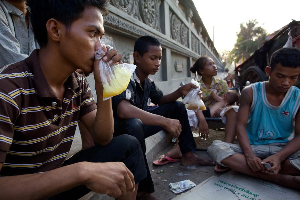 17. Бросс нюхает клей для обуви на лицах Пномпеня. Он живет на улице, как и другие семьи, выживающие только милостыней и собиранием мусора. (Getty Images / Paula Bronstein)