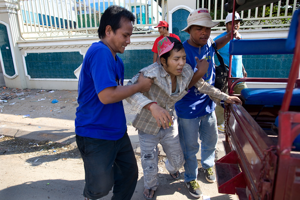 20. Члены организации «Корсанг» помогают наркоману добраться до их автомобиля в Пномпене. Эта некоммерческая организация предлагает помощь наркозависимым людям. (Getty Images / Paula Bronstein)